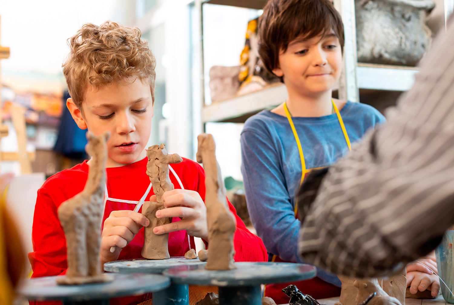 Two talented boys. Two talented boy modeling clay animals at the art lesson near their teacher